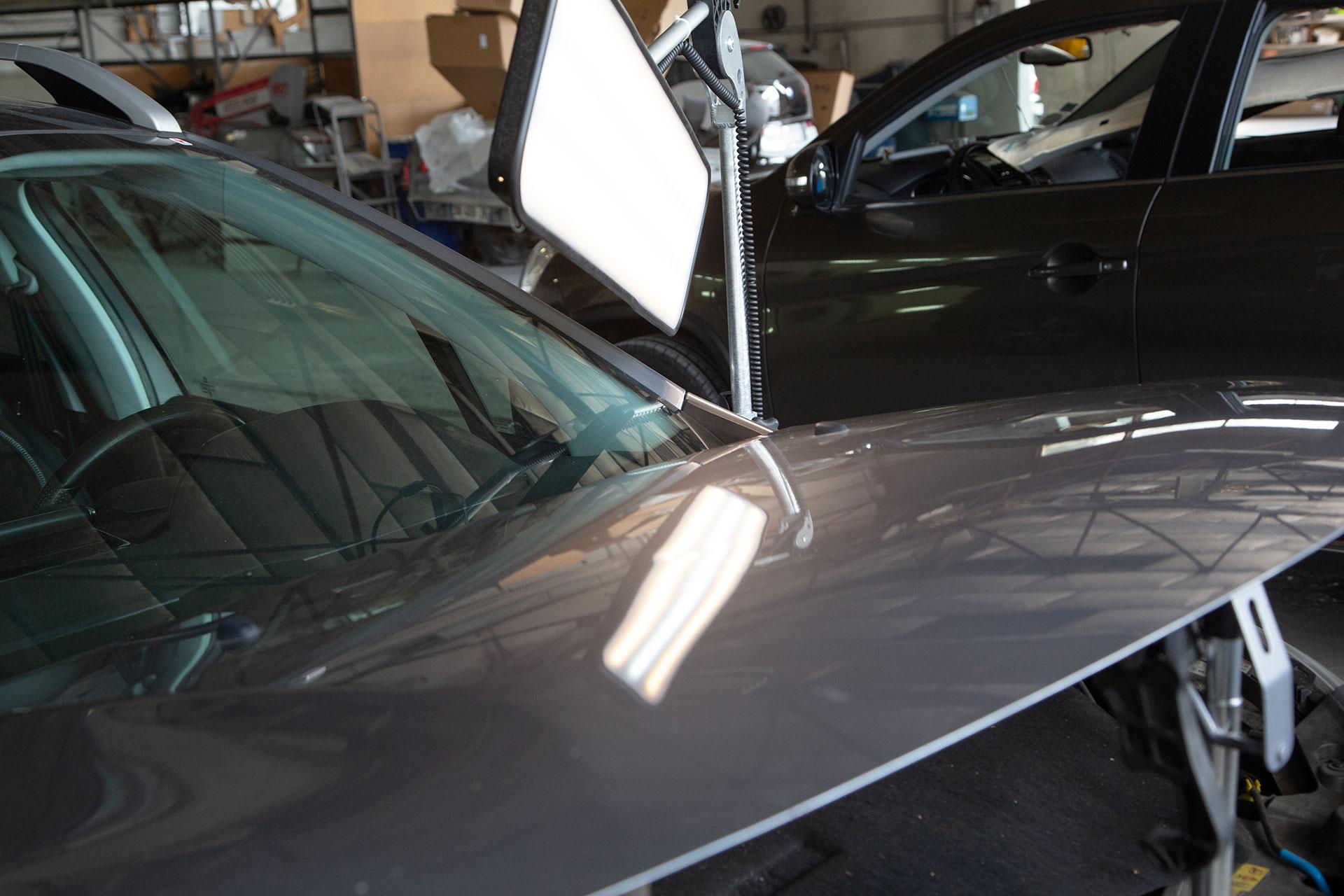 mise en lumière d'un impact de grêle sur un capot de voiture